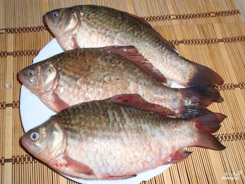 Для начала нам необходимо почистить рыбу. Для этого избавляемся от чешуи, вынимаем внутренности и вырезаем жабры, но оставляем голову. Затем тщательно моем рыбу под холодной водой.