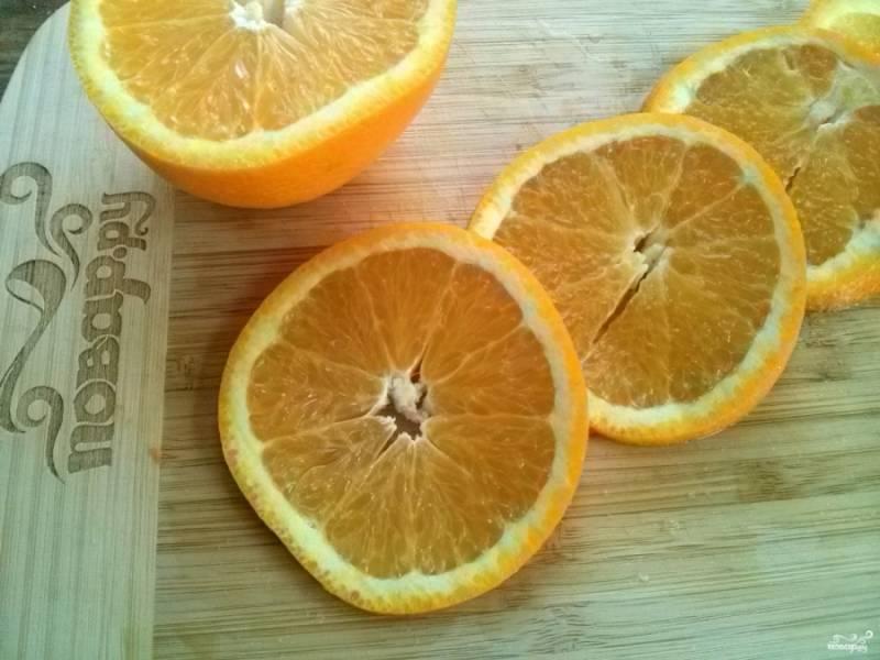 Апельсин тщательно вымойте и половину порежьте тонкими кольцами. Из второй половинки апельсина выжмите сок и смешайте с медом.