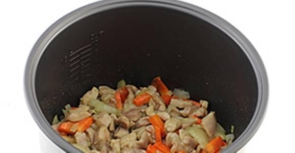 Затем добавьте лук и морковь. Обжаривайте курицу с овощами в течение 10 минут.