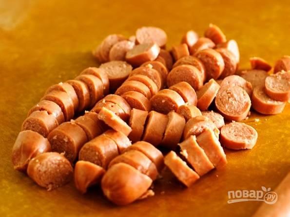 Потом нарежьте колбасу или сосиски. Добавьте её к остальным ингредиентам.
