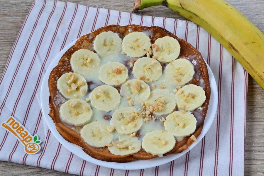 8. Начинаем формировать торт. На плоскую тарелку положите первый блин, смажьте его сгущенкой, выложите тонкие кружочки банана и присыпьте измельченными грецкими орехами (можно использовать и другие орехи).