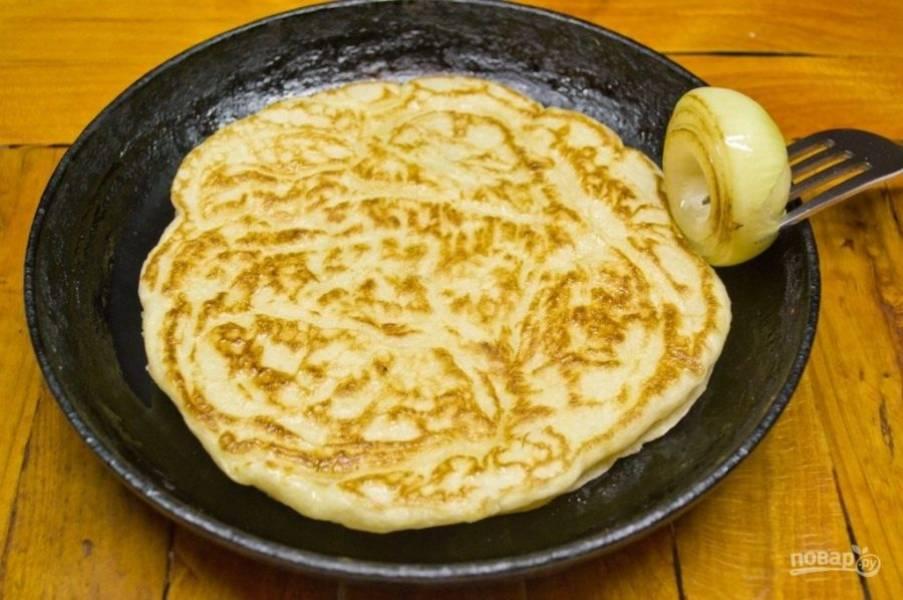 7.Разогрейте сковороду, в отдельную миску налейте немного растительного масла, окуните в нее половинку очищенной луковицы и смажьте сковороду (так вы не нальете масла больше чем нужно). Вылейте тесто, и обжаривайте блинчики с двух сторон.