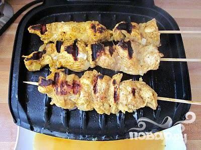 После маринования поместите куриные полоски на шампуры и жарьте.