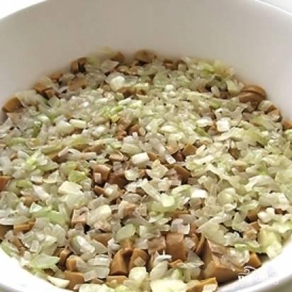 Мелко нарезанный лук слегка поджарить на масле, выложить поверх грибов.
