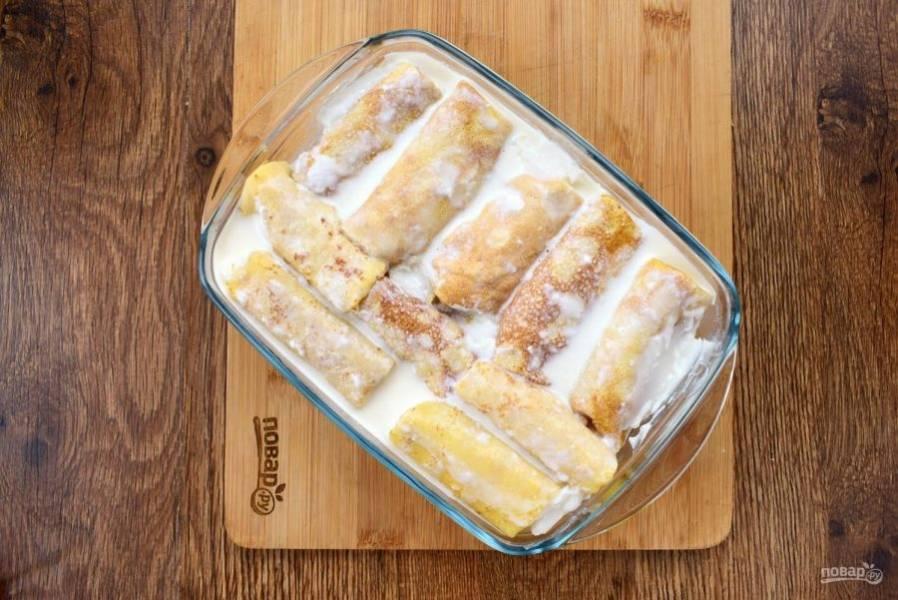 3.    Складывайте блинчики с начинкой в форму для запекания. Для заливки соедините сметану, сахар и залейте блинчики. Поставьте их запекаться в разогретую духовку при 200 °C на 15 минут.