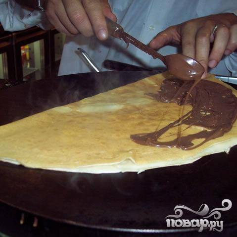 Распространить по поверхности блина шоколадный ореховый крем Nutella.