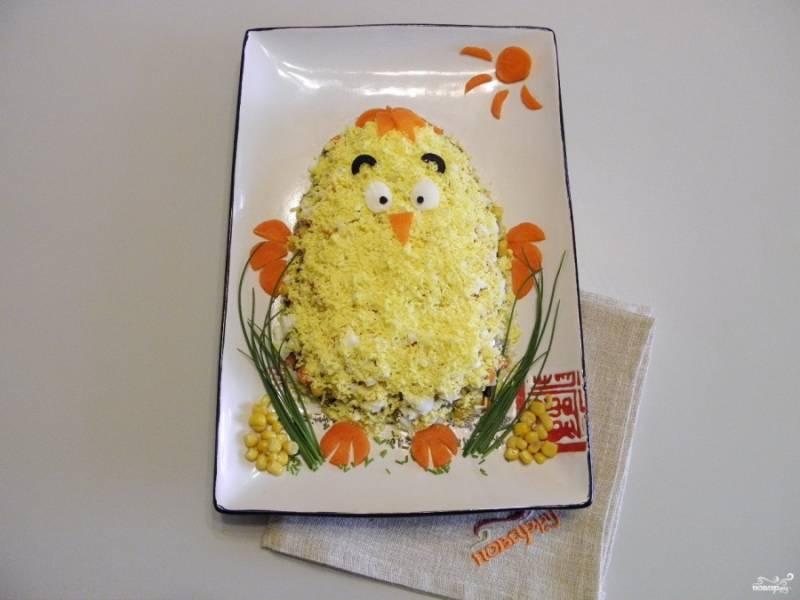 И последний этап — это оформление салата. Сделайте из кусочка белка и маслин глазки, бровки. Из моркови — ножки, крылышки и чубчик. Украсьте салат зеленым луком, зернами кукурузы. Дайте салату настояться минут 10-15, подайте к столу. Светлого Вам праздника!