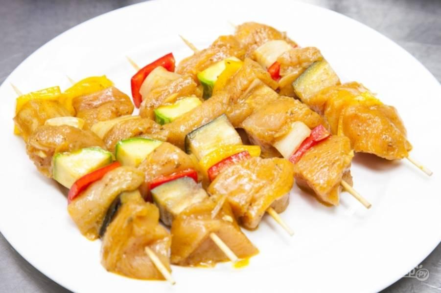 Чередуя овощи и грудку, наденьте их на шпажки или шампуры.