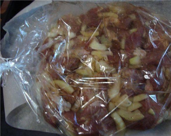 4. Выкладываем мясо поверх лукового слоя. Не перемешиваем! Завязываем пакет, делаем несколько дырочек сверху, и отправим в разогретую духовку на 1.5 - 2 часа!