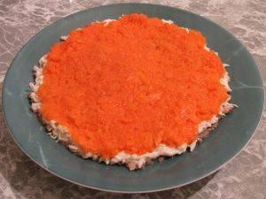 Сверху на белки выложить натёртую морковь и опять смазать небольшим слоем майонеза.