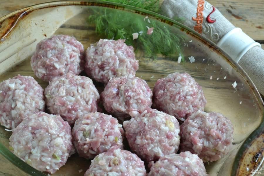 Из свиного фарша с рисом сделайте шарики, положите их в форму, в которой будете запекать.