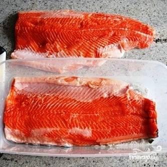 Берем удобную форму для засолки, на дно высыпаем небольшой слой получившейся смеси специй. На этот слой выкладываем одну часть филе рыбы шкурой вниз.
