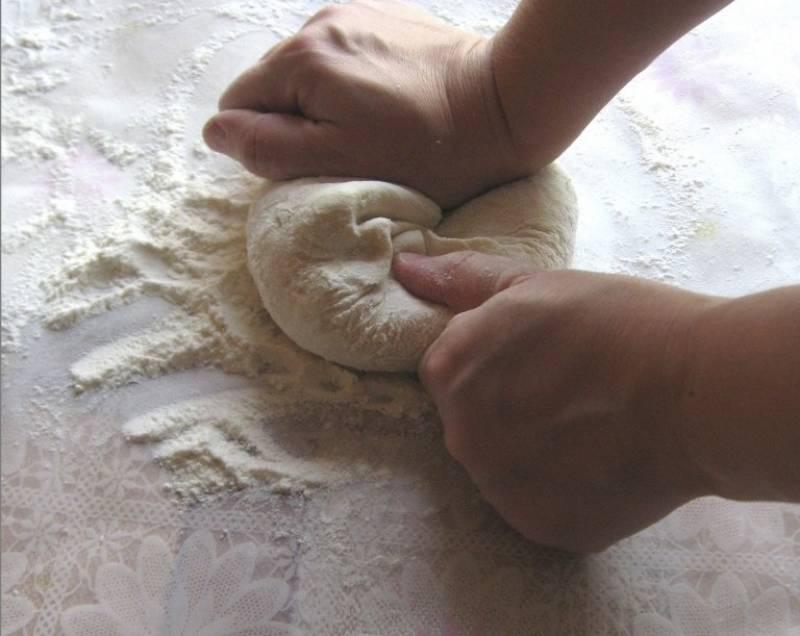 3. Теперь можно постепенно вводить муку и вымешивать крутое тесто. Его нужно не только замесить, но и тщательно взбить и размять руками, чтобы оно было более мягкое и эластичное. На это может потребоваться около 10-15 минут.