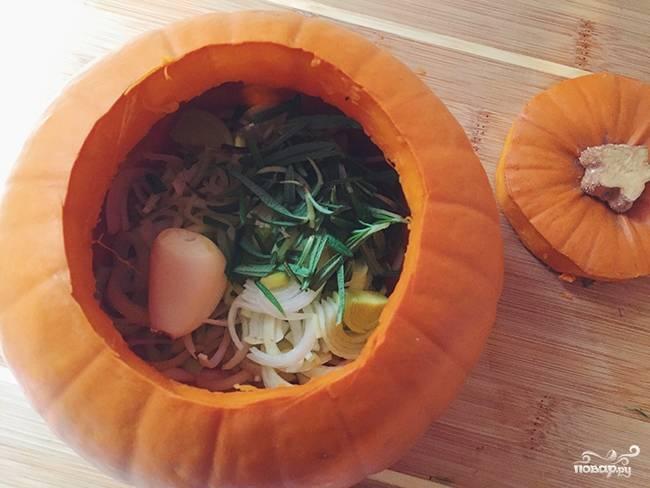 Тыкву помойте, вырежьте аккуратно верхушку, как на Хеллоуин тыквы вырезают. Мякоть тыквы нам пригодится в самом супе. Кстати, семечки тоже можете почистить, обжарить слегка и подавать их вместе с готовым супом. В тыкву выложите порезанный кольцами или полукольцами лук-порей, целый зубчик чеснока, я иногда даже головку целую кладу. Затем розмарин, залейте все бульоном, добавьте специй по вкусу, плавленый сырок размешайте в бульоне. Можете сырок добавить в процессе запекания, так он растворится быстрее и без комочков.