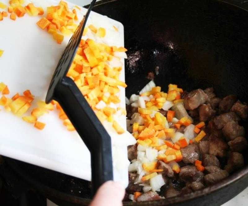 3. Мясо режем небольшими кусочками, и на сильном огне обжарим на растительном масле со всех сторон. Солим, перчим. Когда зарумянится, -  добавим измельченные лук и морковку, жарим на среднем огне под крышкой еще пять минут.