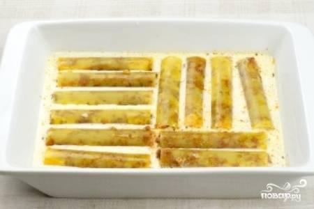 В форму для запекания вылейте половину соуса бешамель, а затем выложите  начиненные каннеллони.