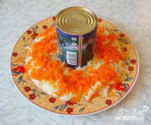 4.Банку из-под оливок можно использовать вместо кольца. В центре блюда устанавливаем банку. Половину куриного мяса выкладываем вокруг банки и немного подсолим. Слегка притрамбовываем каждый слой.   Половинку картофеля натираем поверх мяса, солим и натираем половинку моркови. Натираем яйца поверх моркови. Выкладываем половину потертого сыра. Наносим сетку из майонеза.
