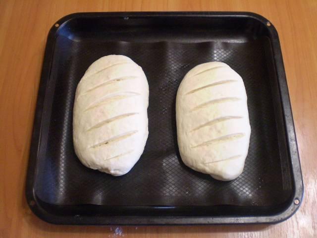 Разделите тесто на две части. Сформируйте хлеб. Для красоты можно сделать надрезы. Оставьте хлеб в тепле еще на 30 минут. После чего поставьте его в духовку на 40 минут выпекаться при 180 градусах.