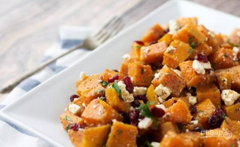 Запекайте тыкву 10 минут, потом перемешайте и готовьте еще 10-15 минут. Затем остудите, смешайте с клюквой, орешками. Присыпьте салат сыром, петрушкой и подавайте.