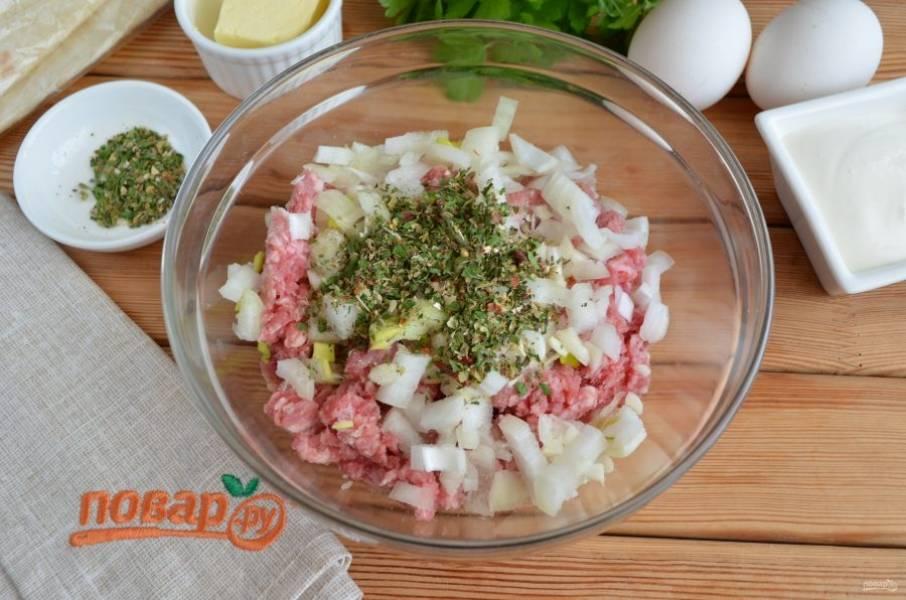 В свино-говяжий фарш добавьте мелко порезанный лук и чеснок, прованские травы, соль. Перемешайте хорошо фарш.