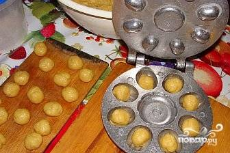 Форму для выпечки орешков нагреваем на плите, смазываем ячейки для скорлупок маслом. Отщипываем небольшие кусочки теста и укладываем в форму. Закрываем форму и выпекаем скорлупки на плите. Выпекать можно и на газовой и на электрической плите.