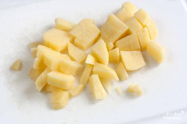 Картофель очищаем, нарезаем небольшими кубиками и кладем в ту же кастрюлю. Варим 10 минут.