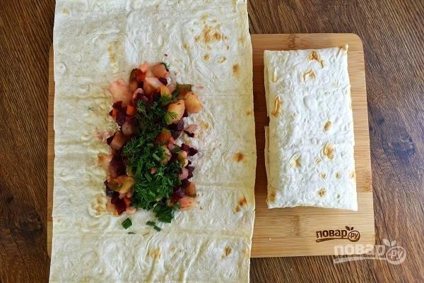 Лаваш разрежьте на 2 части. Положите в центр немного салата, заверните конвертом. Проделайте так со всеми кусочками лаваша.