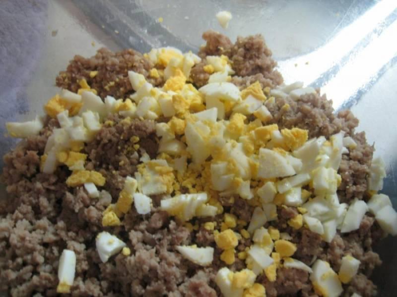 3. Сваренные вкрутую яйца остудить, очистить и нарезать небольшими кубиками. Соединить с фаршем и хорошо перемешать. Луковицу очистить и нарезать мелко. Отправить на сковороду с разогретым маслом и обжарить до золотистого цвета. Добавить к луку вымытые и порезанные небольшими кусочками грибы. Обжарить их до готовности.
