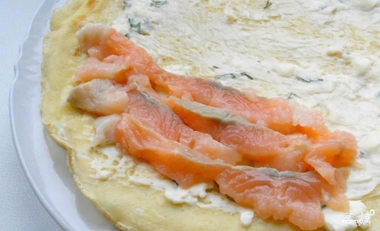 3. Отдельно смешаем плавленный сыр с измельченной зеленью. Каждый блин смажем этой смесью, затем выкладываем кусочки лосося и заворачиваем в рулет.