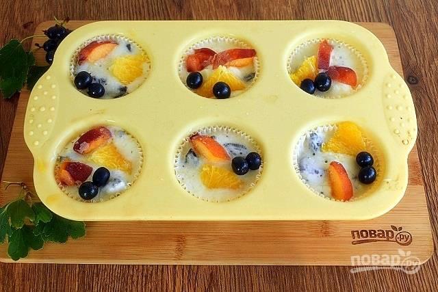 Пергаментные корзиночки для кексов поместите в силиконовые формы, чтобы при наполнении они не потеряли форму. На дно каждой корзинки уложите по одному печенью. Йогурт перемешайте с кусочками оставшегося измельченного печенья, наполните этой смесью корзиночки. Сверху положите кусочки фруктов и ягоды. Поставьте в морозильник минимум на 4 часа.