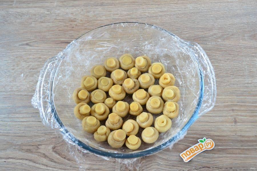 Большую миску с плоским дном (или кастрюлю) застелите пищевой пленкой – так будет удобнее переворачивать салат. На дно выложите маринованные шампиньоны шляпками вниз.