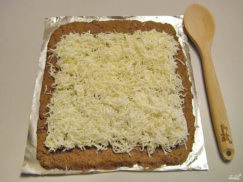 Сверху распределите тертый плавленый сыр. Только отступите от ближнего края 1-2 см., а от края дальнего — 2-3 см.