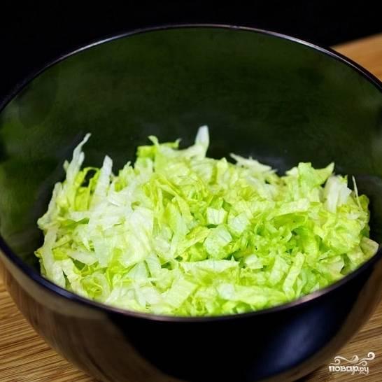 Нашинкуйте листья салата в глубокую салатницу.