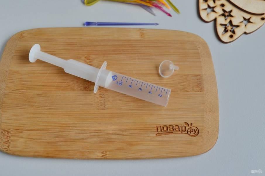 Возьмите стерильный шприц. Чем больше кубиков, тем более устойчивыми будут закусочки на шпажках. Отрежьте ровно ту часть, на которую одевают иглу.