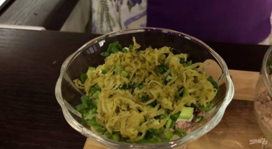 3.  Сверху выложите слой картофеля, затем слой измельченной печени трески и разровняйте. Смажьте майонезом, выложите нарезанный зеленый лук, маринованные огурцы и свежие огурцы.