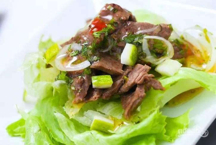 4.Выкладываю на салатные листья кусочки мяса, поливаю соусом, в котором мариновалось мясо, посыпаю огурцами и кладу дольки черри. Подаю салат сразу после приготовления.