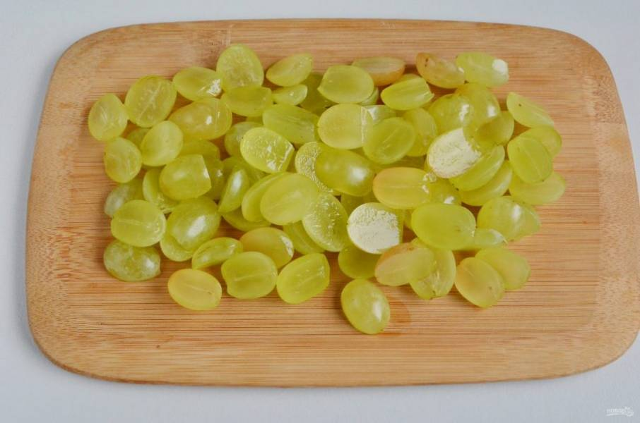 Пока желатин растворяется, можно подготовить виноград. Каждую ягодку порежьте на половинки, удалите косточки. У меня сорт без косточек, поэтому я просто порезала на половинки.