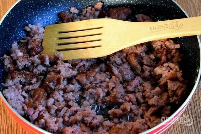 В глубокой сковороде разогрейте масло и на сильном огне обжарьте мясной фарш до румяной корочки в течение 5 минут. Уменьшите огонь до среднего. Фетуччини отварите в кипящей соленой воде согласно инструкции на упаковке.