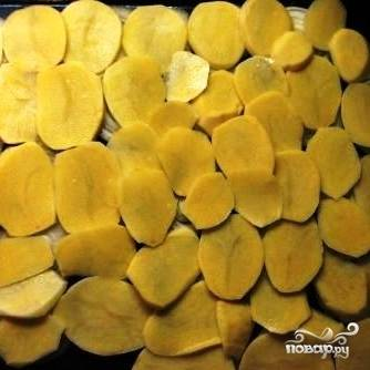 Картофель чистим, нарезаем тонкими ломтиками и выкладываем на лук.