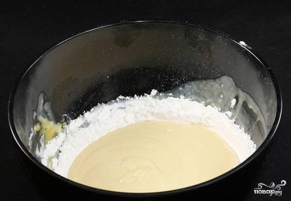 3. В глубокую мисочку параллельно просейте пару стаканов муки. Вылейте туда яичную смесь. Добавьте соль и соду.