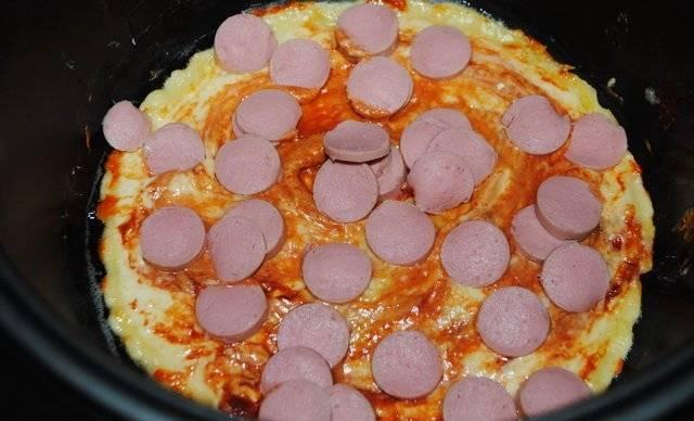 Далее смазываем блин из теста томатной пастой и выкладываем на него нарезанные кружочками сосиски.