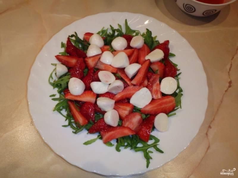 Остальную клубнику порежьте крупно и выложите поверх рукколы.  Моцареллу порежьте пополам и добавьте в салат.