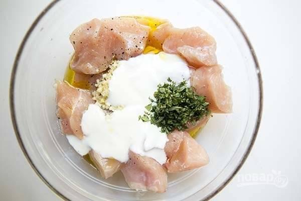 1. Вымойте и обсушите грудку, нарежьте средними кубиками. В глубокой мисочке соедините с солью, йогуртом, измельченным чесноком и орегано, соком лимона, маслом и перцем.