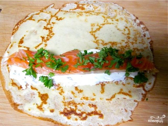 Каждый блинчик заправляем сыром (аккуратно размазываем сыр приблизительно в центре блина), пластом семги и рубленой зеленью. Скручиваем в трубочку.