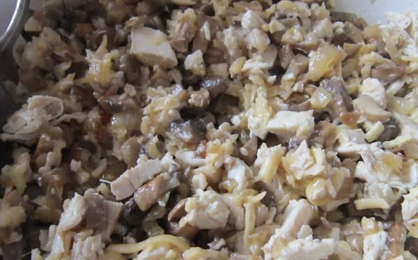 Смешиваем подготовленное куриное мясо с обжаренными с луком грибами. Чтобы начинка не высыпалась из блинчиков, можно добавить натертый на терке сыр. При обжаривании блинчиков он растает и скрепит между собой все ингредиенты начинки.