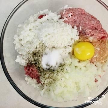 1. Включите духовку нагреваться на 200 градусов. Рис промойте кипятком. В большой миске смешайте ингредиенты для приготовления ежиков: мясной фарш, рис, две мелко нарезанные луковицы, яйцо, воду, соль и перец.