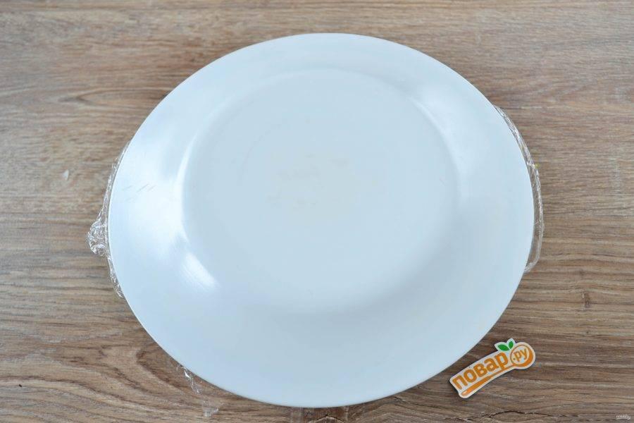 Накройте все плоской тарелкой и аккуратно переверните миску с салатом, чтобы грибы оказались сверху.