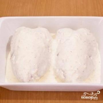 2.Куриные грудки хорошо промыть и немного обсушить. Отделить от мяса косточку. Можно этого не делать, но просто мясо есть намного удобнее. Положить приготовленные грудки в форму для запекания и залить их нашим сметанным соусом.