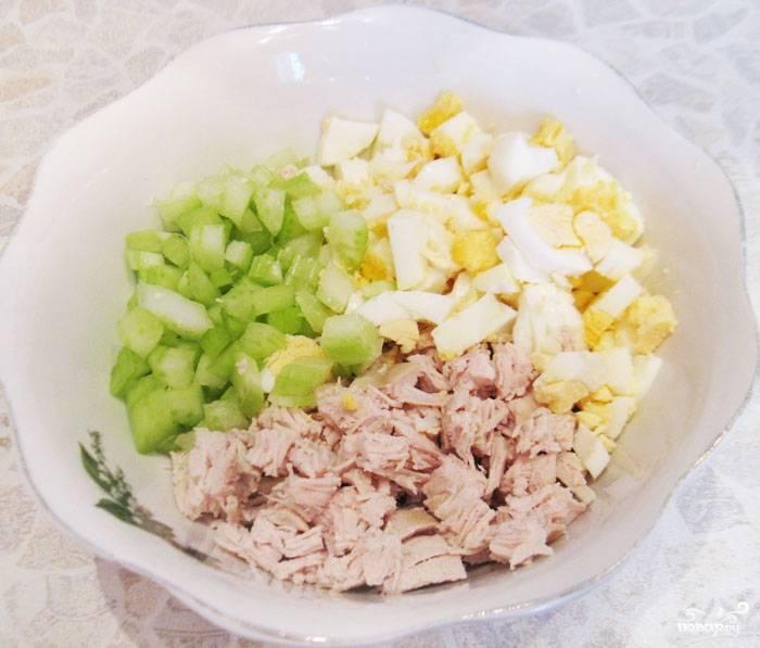 Тем временем смешиваем в миске отварную курицу, кубиками нарезанные яичные белки (желтки оставляем для украшения), мелко нарезанный сельдерей.