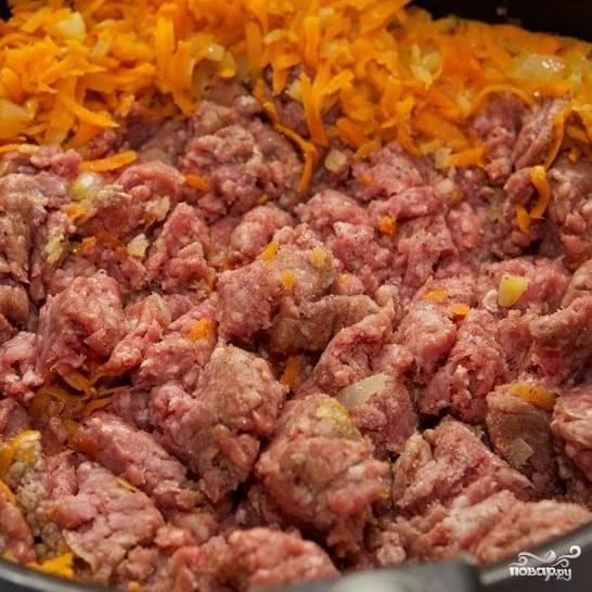 Добавляем в жаровню говяжий фарш, разминаем его лопаткой, перемешиваем с овощами.